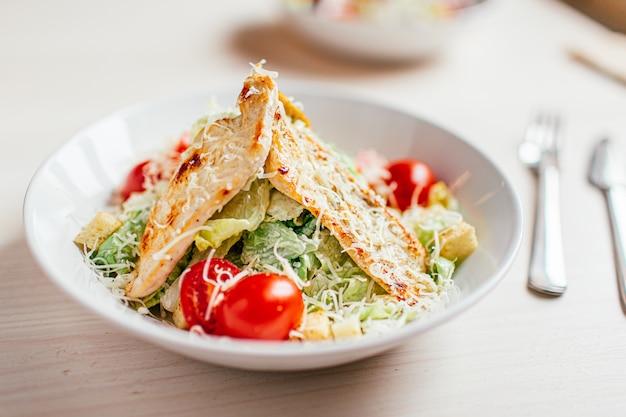 Caesarsalade met kip op witte houten tafel met vork en mes.