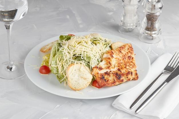 Caesarsalade met kip, parmezaanse kaas en tarwecroutons op wit