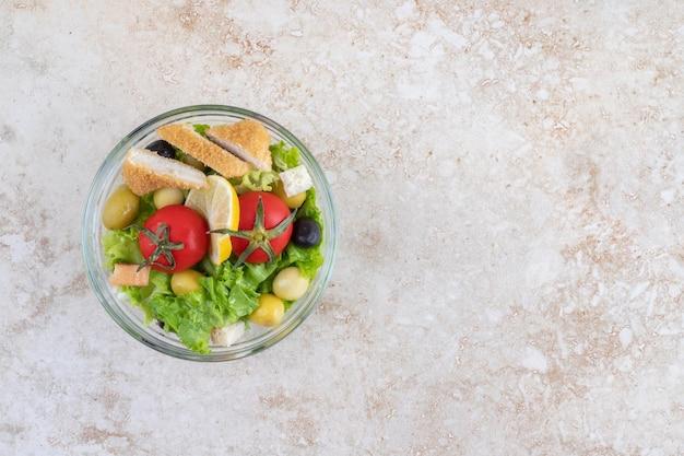 Caesarsalade met kipnuggets, kruiden en kerstomaatjes.