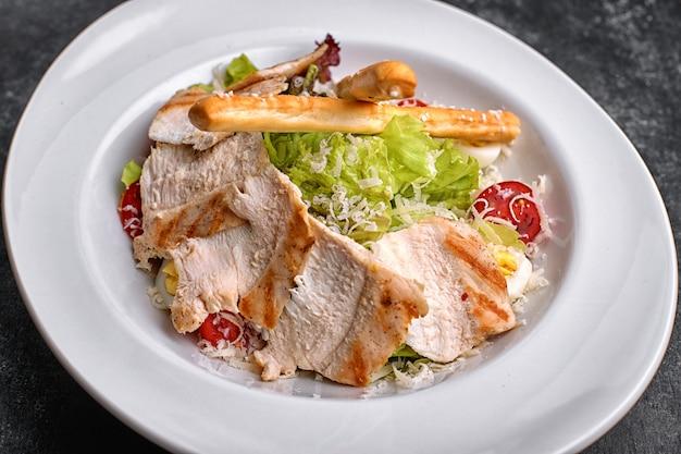 Caesarsalade met kippenvlees, sla, tomaten, kaas en eieren, op een witte plaat
