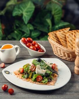 Caesarsalade met kruiden, cherry tomaten en toastbrood.