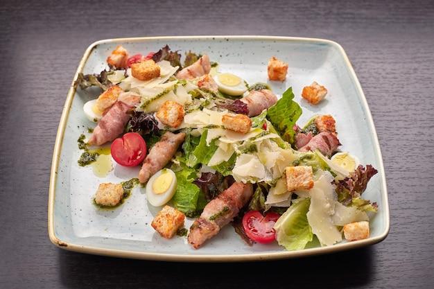 Caesarsalade met kruidenkip-spek-eieren en tomaten op een vierkante lichte plaat op een donkere achtergrond