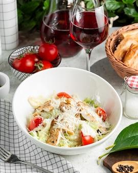 Caesarsalade met tomaat, sla, geserveerd met wijn