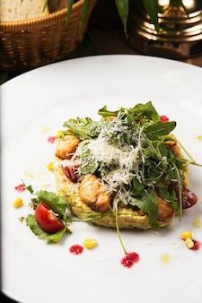 Caesarsalade met verse groente en kip. salade in witte plaat op houten tafel, heerlijke salade