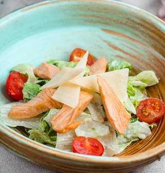 Caesarsalade met visfilet, sla, gesneden parmezaanse kaasplakken en tomaten.