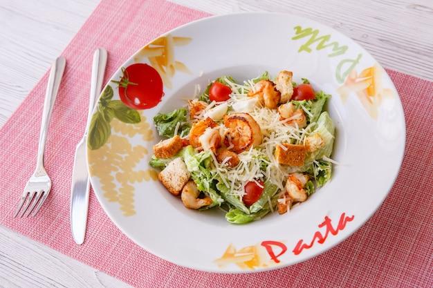 Caesarsalade met zeevruchten, op het bord staat pasta.
