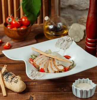 Caesarsalade van kip gegarneerd met parmezaanse kaas en broodstikcs