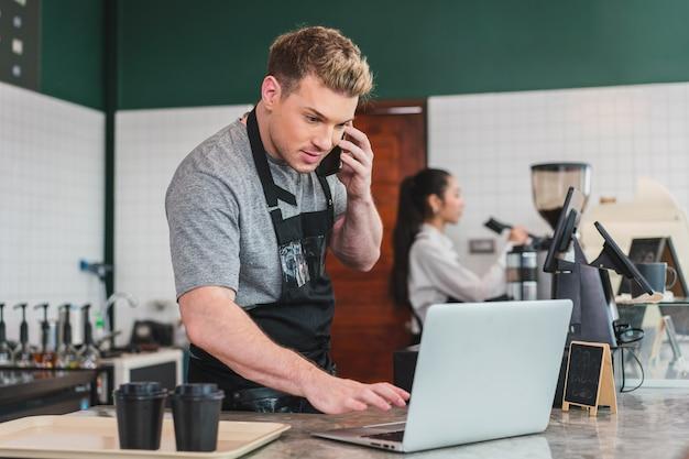 Cafe-eigenaar barista ontvangt bestelling van klant op smartphone terwijl hij computer gebruikt bij koffie