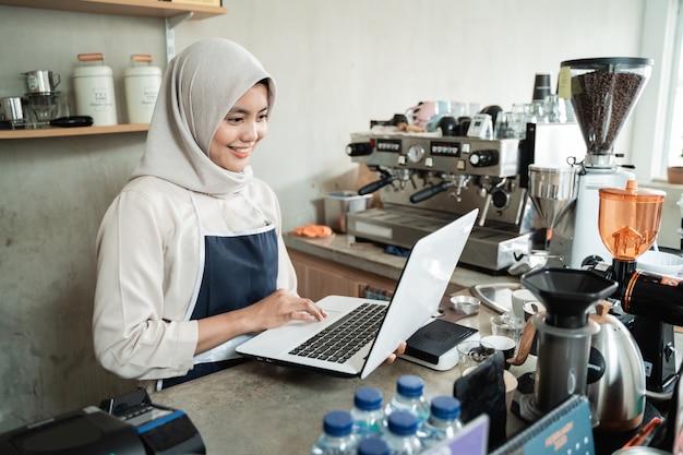 Cafe-eigenaar hijab-vrouwen gebruiken laptop