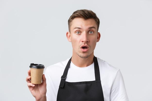 Café en restaurants coffeeshop eigenaren en retail concept geschrokken en verward barista ober in zwarte schort met papieren beker met afhaalmaaltijden drankje witte muur