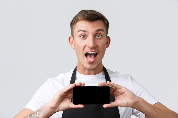 Café en restaurants coffeeshop eigenaren en winkelconcept opgewonden en verbaasd knappe verkoper in zwarte schort open mond geamuseerd en toont applicatie smartphone display witte muur
