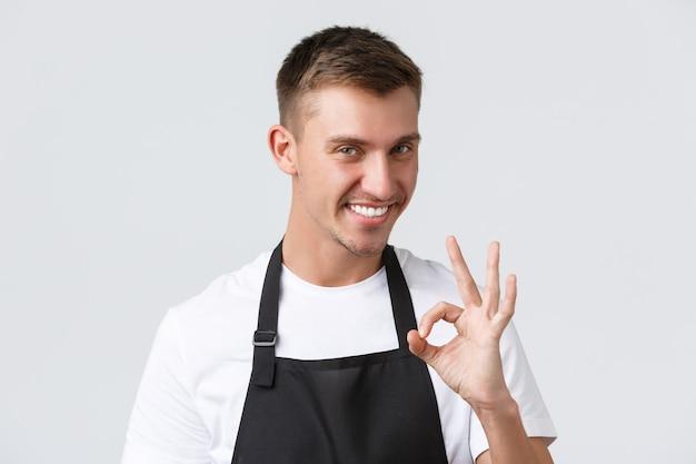 Café en restaurants, eigenaren van coffeeshops en retailconcept. close-up van brutale knappe ober in zwarte schort, barista garandeert kwaliteit van drankjes, toont goed teken en glimlacht tevreden