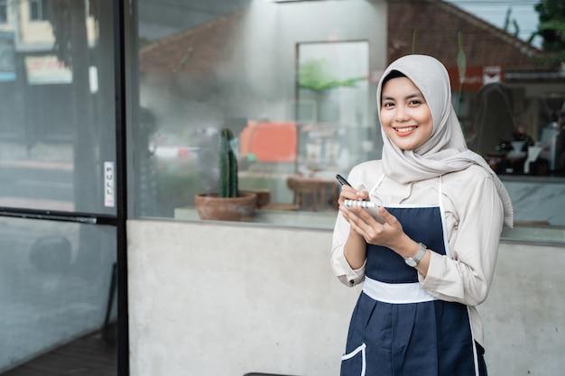 Cafe gesluierde serveerster permanent met houden een pen en notitie