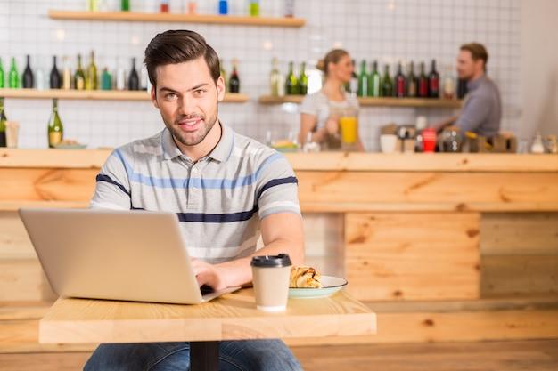 Cafe klant. vrolijke positieve aardige man zit aan tafel en werkt op de laptop tijdens de lunch