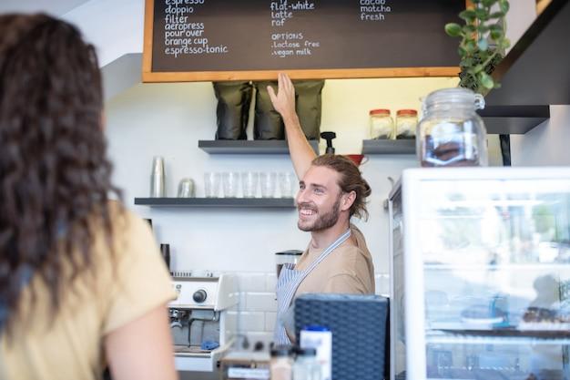 Café, koffieselectie. vrolijke jonge bebaarde man in schort wijzend op menu met verscheidenheid aan koffie opknoping op de muur en dames terug