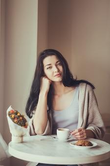 Cafe stad levensstijl vrouw drinken en eten binnenshuis zittend in trendy stedelijk café. cool jong
