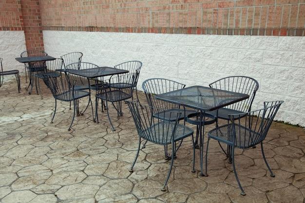 Cafe tafels en stoelen buiten een stenen gebouw.