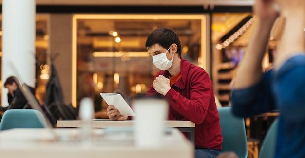 Cafébezoekers met beschermende maskers werken op hun laptops. persoonlijke hygiëne en gezondheidszorg