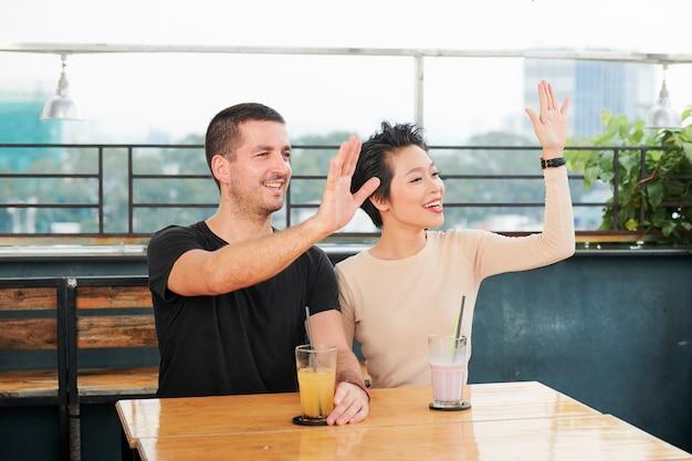 Cafébezoekers zwaaien met handen