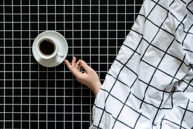 Cafeïne en slaapproblemen. koffie drinken voor het slapengaan. een kopje zwarte koffie op een zwarte geruite achtergrond.