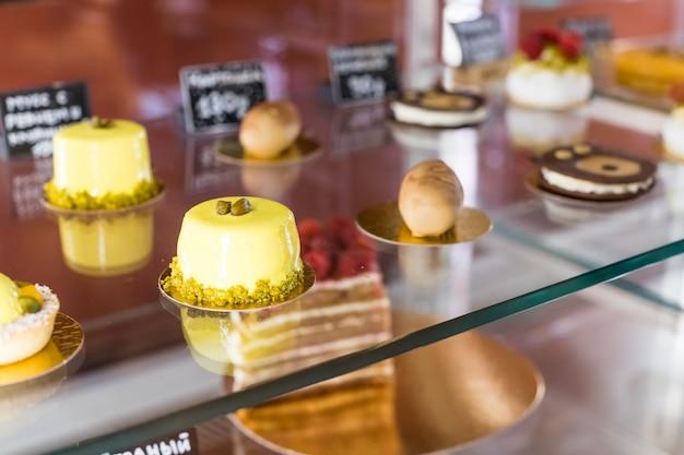 Cafetaria, bakkerij met verschillende soorten bakker zoals koekjes, gebak, gebak, winkelgebied. verschillende desserts en gebak in het raam van een patisserie. selectieve aandacht. patisserie