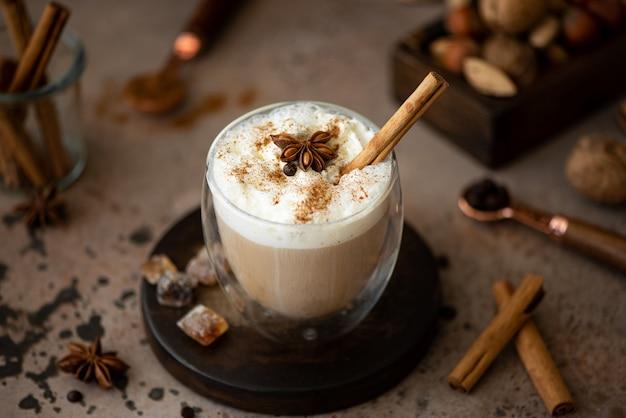 Caffe latte met slagroom, kaneel en anijs in een glas