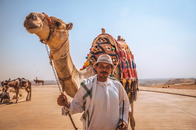 Caïro, egypte; oktober 2020: portret van een lokale verkoper met zijn kameel bij de kefren-piramide. de piramides van gizeh, het oudste grafmonument ter wereld