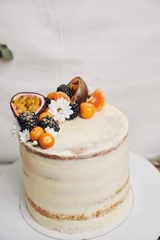 Cake met bessen en passievruchten achter een wit