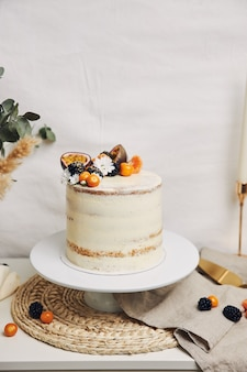 Cake met bessen en passievruchten naast een plant achter een wit