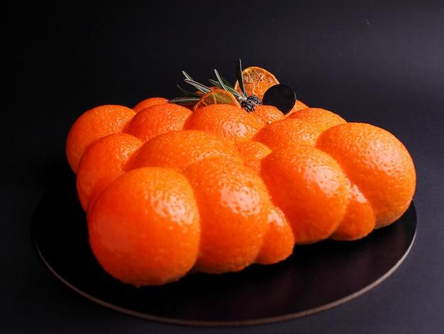 Cake met bessenmousse in de spiegel oranje glazuur ingericht