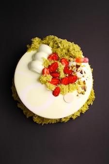 Cake met bessenmousse in de spiegelglazuur. met aardbei en moleculaire koekjesdecoratie. op de zwarte achtergrond.