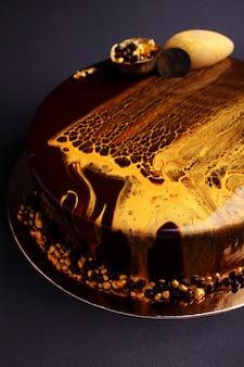 Cake met bessenmousse in de spiegelglazuur. op de zwarte achtergrond.