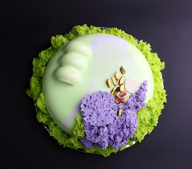 Cake met bessenmousse in de spiegelglazuur versierd met een moleculair koekje. op de zwarte achtergrond.