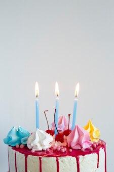 Cake met glazuur en aangestoken kaarsen