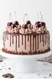 Cake met koffie, kaas, kersen en chocolade topping op een witte caketribune