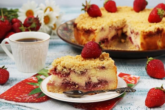 Cake met kwark met aardbeien bevindt zich op een blauw oppervlak, een fluitje van een cent bevindt zich op de voorgrond op een bord, horizontale foto