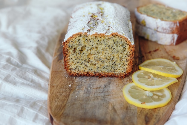 Cake met maanzaad en citroenschil, bestrooid met poedersuiker. cupcake met citroen op een houten bord.