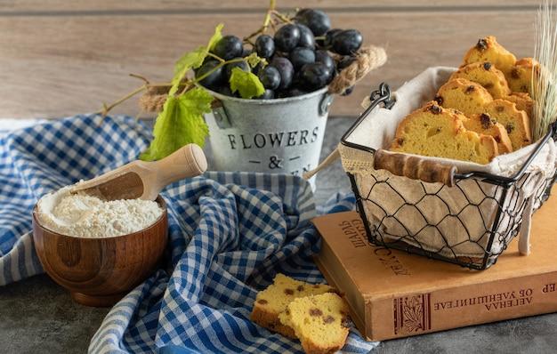 Cake met rozijnen, bloem en druiven op marmeren tafel met boek