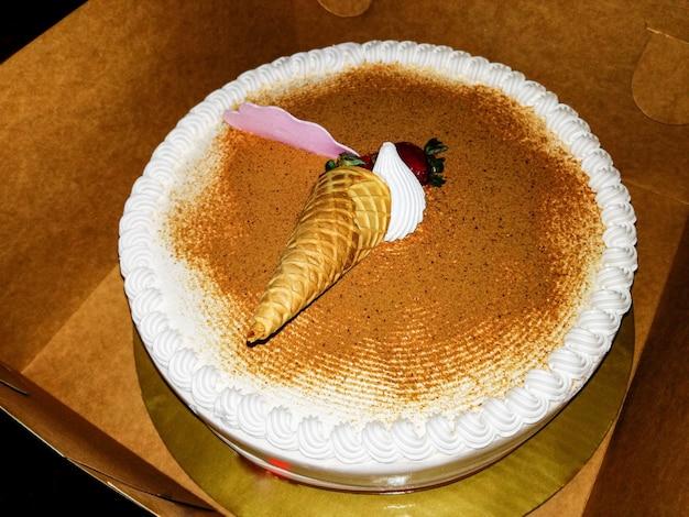 Cake met slagroom en gedecoreerd met een ijshoorntje en een aardbei