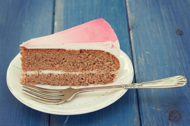 Cake op witte plaat op blauw