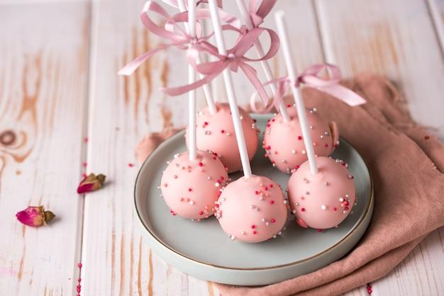 Cake pops in roze crème liggen op een prachtig bord. heerlijk close-up dessert.
