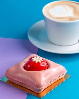 Cake roze mousse cake met kopje koffie op blauw en paars