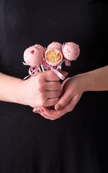 Cake springt in de handen van vrouwen op een zwarte achtergrond. dessert in roze chocolade crème met poeder en boog.