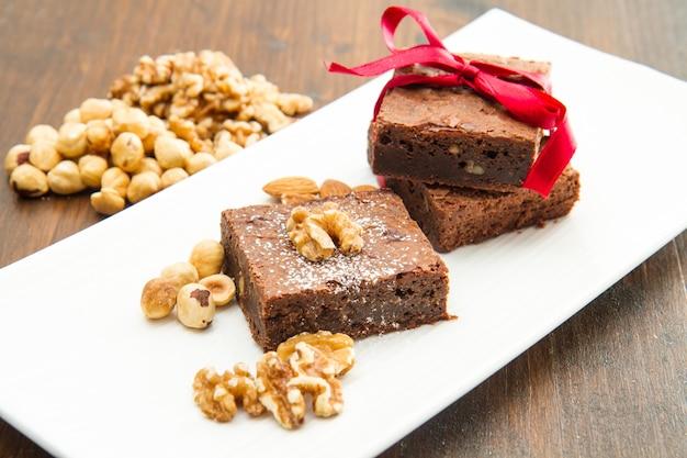 Cakechocolade brownies op witte schotel met noot