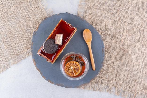 Cakeplak, glas thee en lepel op donker bord. hoge kwaliteit foto