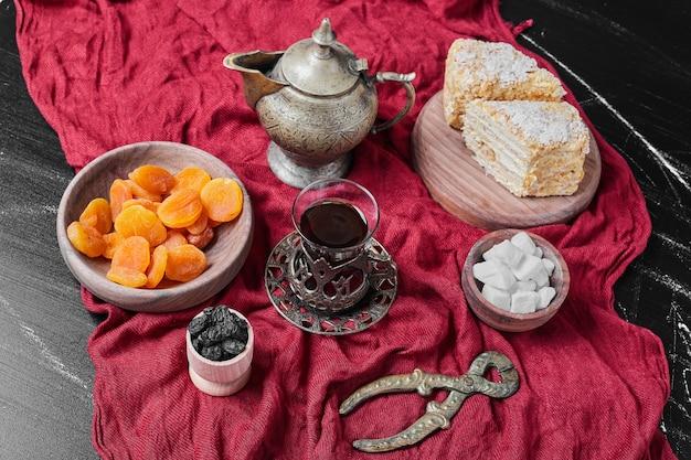 Cakeplakken op rode handdoek met thee.