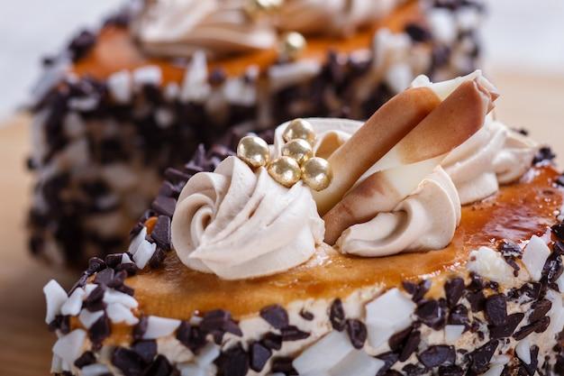 Cakes met chocoladeschilfers en roomdecoratie op houten raad op witte achtergrond