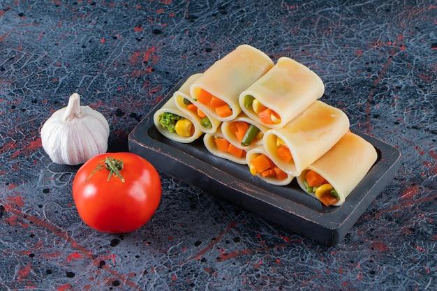 Calamarata pasta gevuld met gehakte groenten op zwarte plaat.