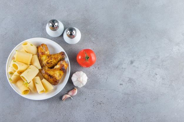 Calamarata pasta met gebakken kippenvleugels op witte plaat.