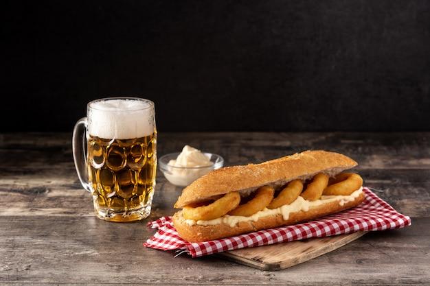 Calamari ringen sandwich en bier op houten tafel